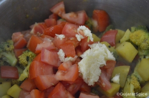 Chopped tomatoes and garlic added to vegetables